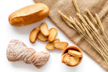 Cuire le pain avec de la farine de blé et des oreilles sur fond blanc de table dans la vue de dessus de la boulangerie Banque d'images - 85980085
