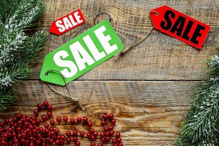 christmas gift: Christmas sale. Sale labels near spruce branch and xmas decor on wooden background top view.