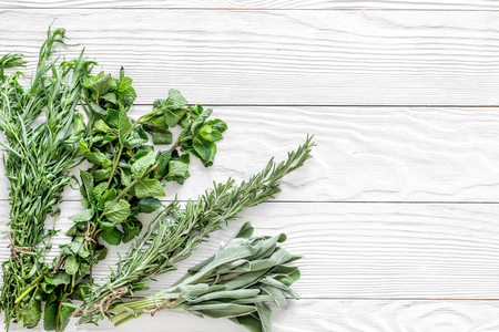 fresh herbs and greenery for spices and cooking on white wooden kitchen desk background top view mock up Stock fotó