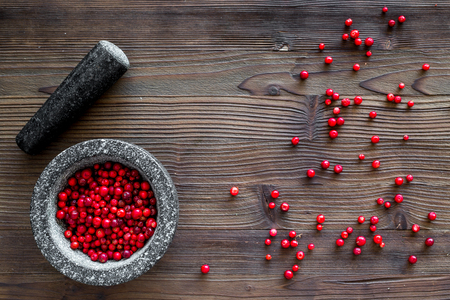 mortar with berries, herbs and spices ingredients on wooden desk background top view