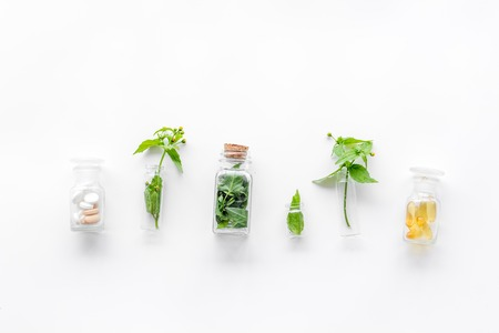 Medicinal herb in bottles on white background top view.