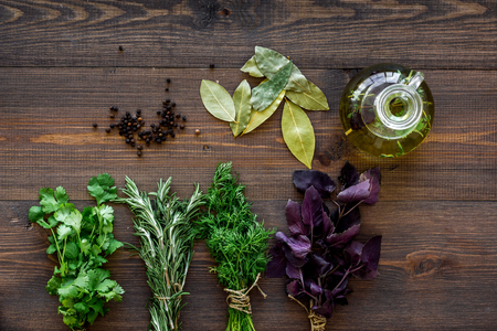natural oil and fresh greenery for restaurant cooking with spices on wooden kitchen table background top view Banco de Imagens - 85980217