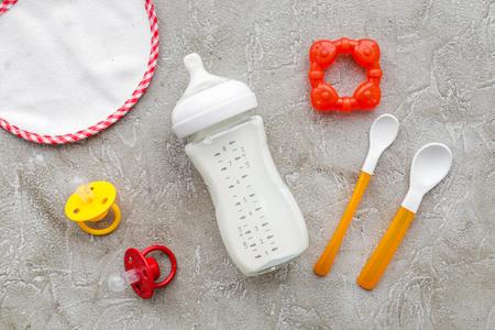 Preparación de mezcla de bebé con leche de bebé de la leche de mascar en la cuchara de madera y juguetes en la pared de piedra gris vista superior Foto de archivo - 85980251