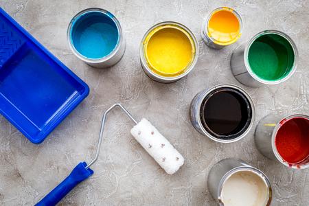 塗装の準備。塗料、ローラー、グレーのトレイは石背景トップ ビューです。