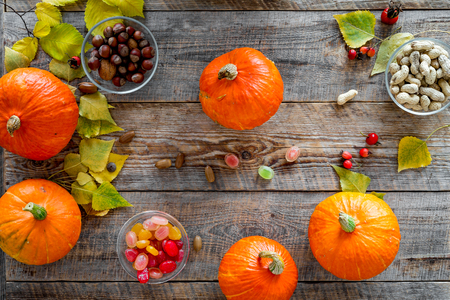 Pumpkin harvest. Pumpkins near nuts and autumn leaves on wooden background top view.