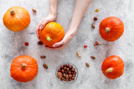Pumpkin harvest. Pumpkins near nuts on grey background top view. Stock Photo