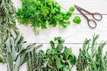 drogen van verse kruiden en groen voor spice thuis eten op witte houten keuken bureau achtergrond bovenaanzicht Stockfoto