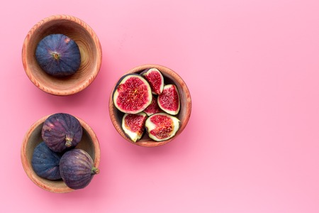 Fresh blue figs in bowls on pink background top view.