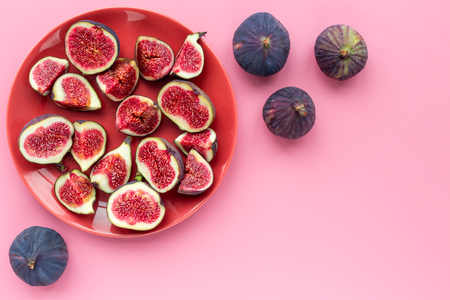 Fresh blue figs sliceson plate on pink background top view. 版權商用圖片