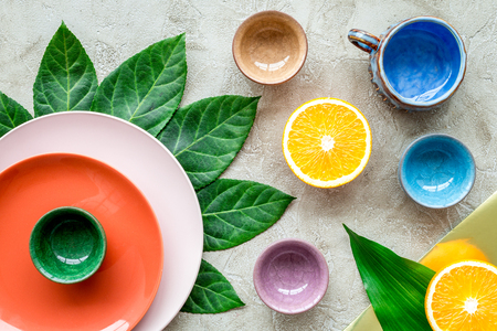 Tableware pattern. Cups and plates decorated by exotic leaves and fruits on grey background top view. Stock Photo
