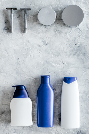 Shampoo and shower gel for men on grey stone background top view.
