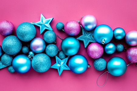 Christmas toys. Pink and blue balls and stars on pink background top view.
