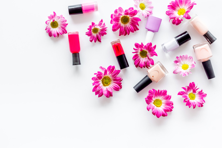salon: Choose nail polish for manicure. Bottles of colored polish on white background top view.