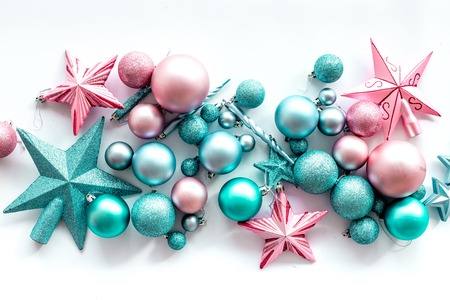 Christmas decoration concept. Pink and blue stars and balls near pine branches on white background top view.