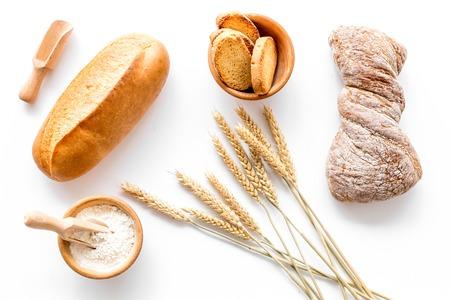 Pain savoureux frais avec des plantes de blé dans la boulangerie sur le dessus de la vue de dessus de fond de bureau blanc Banque d'images - 86210047
