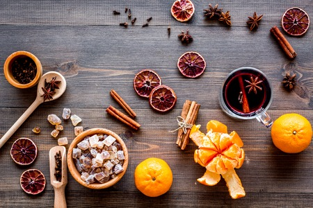 Merry christmas in winter evening with warm drink. Hot mulled wine or grog with fruits and spices on wooden desk background top view Stock Photo