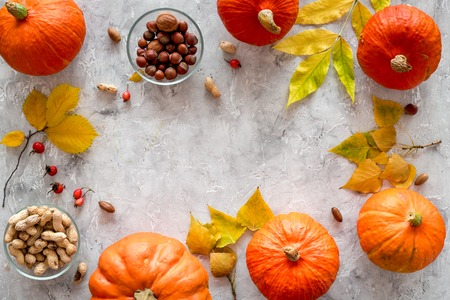 Pumpkin harvest. Pumpkins near nuts and autumn leaves on grey background top view copyspace