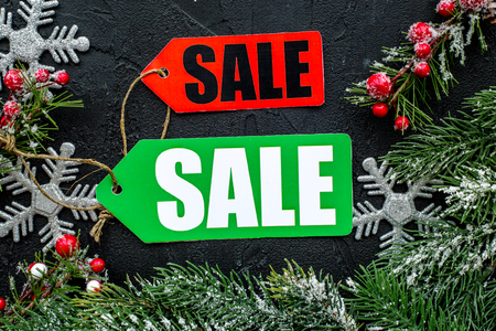 Winter sale. Sale labels near spruce branches on black background top view. Archivio Fotografico