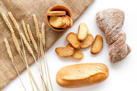Pain savoureux frais avec des plantes de blé dans la boulangerie sur le dessus de la vue de dessus de fond de bureau blanc Banque d'images - 86298548