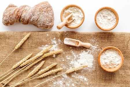 白いデスク ベーカリー トップ ビューで背景に耳から小麦とライ麦粉の生産