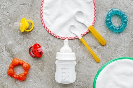 Enfants nourrir avec du lait à la chaux ou le bébé de la boîte à lunch du lait et jouets sur fond gris table vue de dessus Banque d'images - 86538502