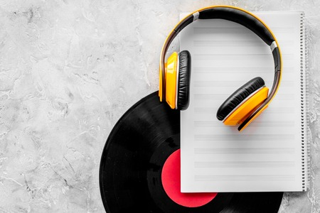 Compose music. Vinyl records, headphones, music notes on grey background top view. Stock Photo