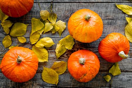 Pumpkin harvest. Pumpkins among autumn leaves on wooden background top view