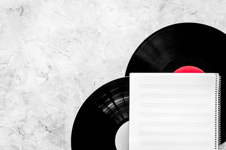 Workplace of musician. Music notes, vinyl record and coffee on grey background top view copyspace