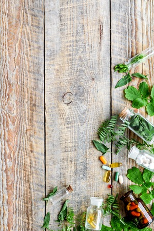 Healing herbs. Fresh leaves, bottles and pills on wooden background top view. Reklamní fotografie