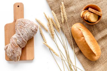 Pain de cuisson avec de la farine de blé et des oreilles sur fond blanc table dans la vue de dessus de la boulangerie Banque d'images - 86622888