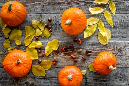 Pumpkin harvest. Pumpkins among autumn leaves on wooden background top view.