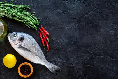Cooking dorado fish. Black background top view.