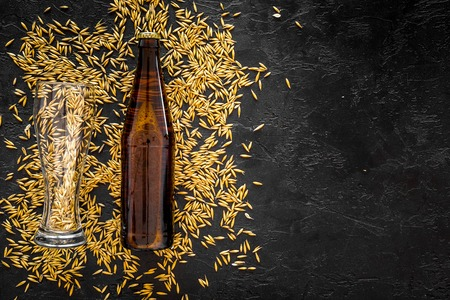 Grains of malting barley near beer bottle on black background top view. Stock Photo