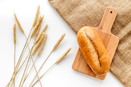 Pain de cuisson avec de la farine de blé et des oreilles sur fond blanc table dans la vue de dessus de la boulangerie Banque d'images - 86733064