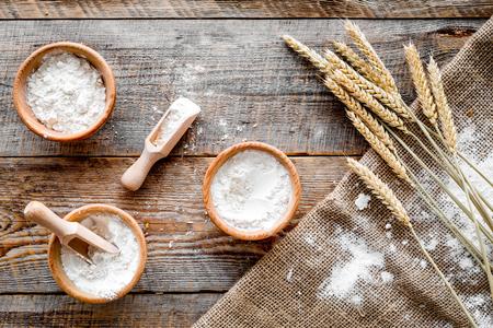 木製デスク背景トップ ビューのパン屋さんの小麦粉の生産のためのコムギとライムギ耳