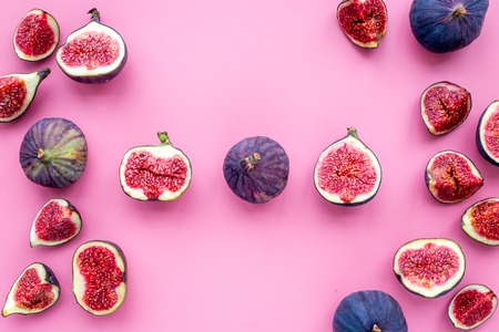 Fresh blue figs on pink background top view.