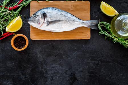 Preparing fresh sea fish. Black background top view.