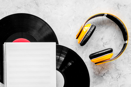 Workplace of DJ. Vinyl records, headphones, music notes on grey background top view