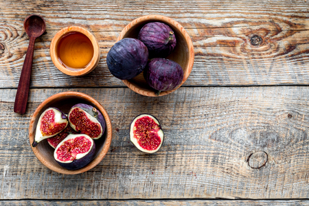 Fresh blue figs in bowl and honey on wooden background top view copyspace Banco de Imagens