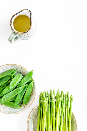 Fresh green pea pods and sprout of asparagus on white background top view. Stock Photo