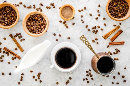 커피 콩, 우유 및 회색 배경 계 피 위에 블랙 커피 잔의 상위 뷰