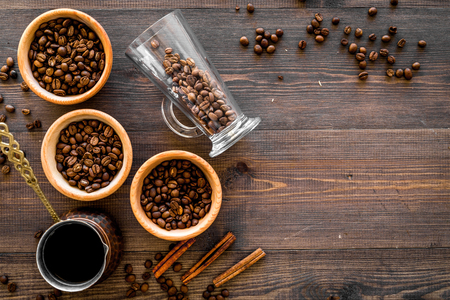 Brew coffee in turkish coffee pot. Wooden background top view copyspace