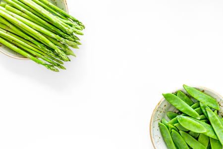 Fresh green pea pods and sprout of asparagus on white background top view copyspace