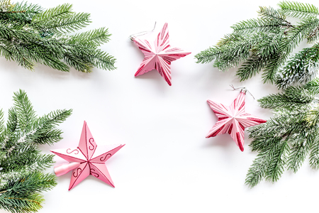 Christmas toys. Pink stars near pine branches on white background top view. Stock Photo