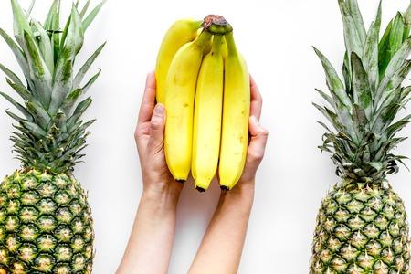 Tropische vruchten achtergrond. De bananen van de handgreep tussen ananas op witte hoogste mening