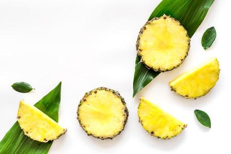 Tropisch fruit concept. Patroon van pinneapple plakjes en bladeren op witte achtergrond bovenaanzicht copyspace