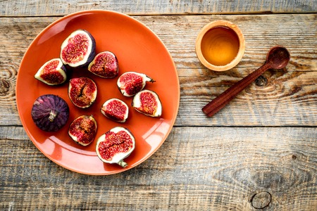 Plate of fresh blue figs and honey on wooden background top view copyspace Banco de Imagens - 86960172