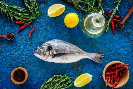 Dorado fish with spices ready to cook on blue background top view