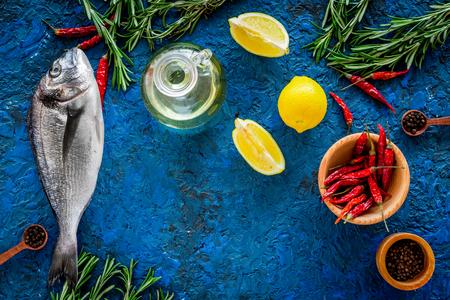 Dorado vis met kruiden klaar om te koken op blauwe achtergrond bovenaanzicht.