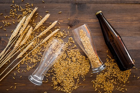 Preparing beer. Barley near beer bottle and glass on wooden background top view. Stock Photo - 86960192